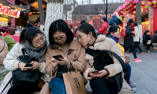 Chinese users looking at a mobile phone.